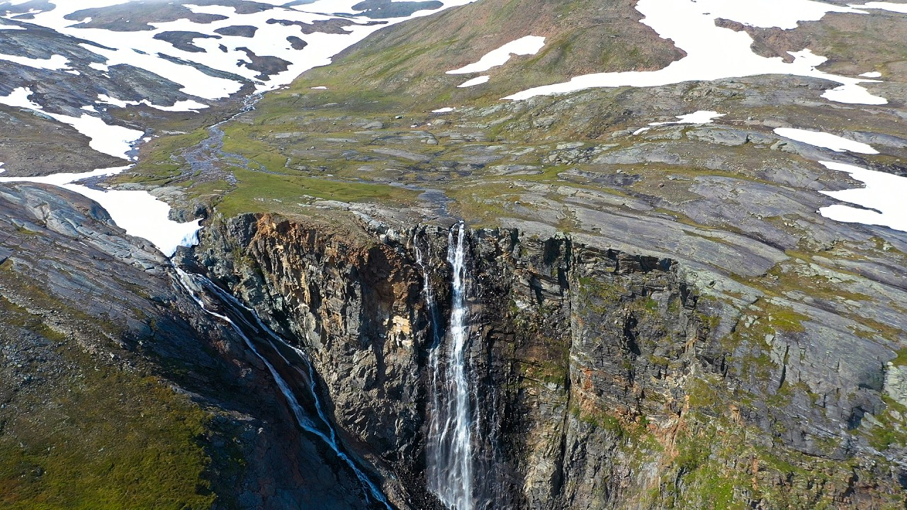 Free stock footage: Flying away from a waterfall in the mountains