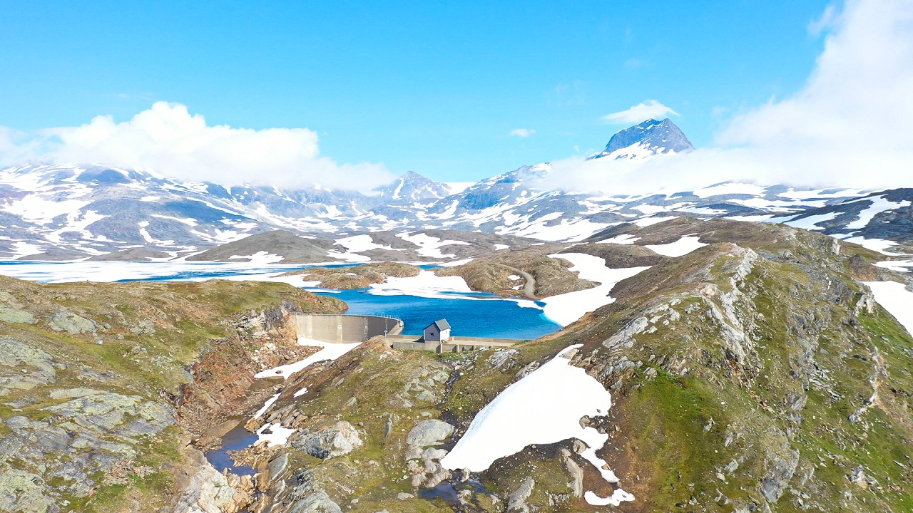 Free stock footage: Flying towards a dam in the snowy mountains