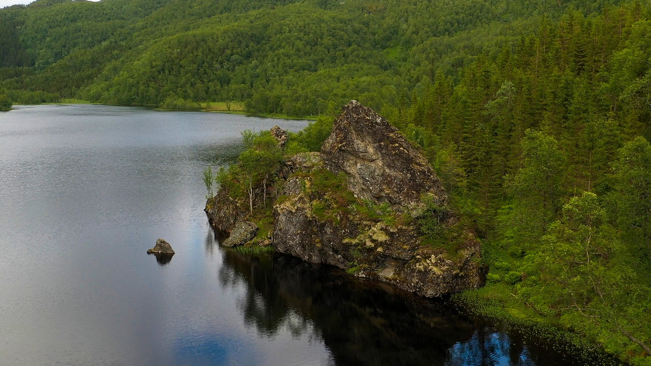 Free stock footage: Flying past a rock formation by a lake