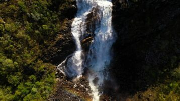 Free stock footage: Flying upwards from a large forest waterfall
