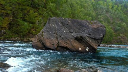Free stock footage: River flowing around a big boulder